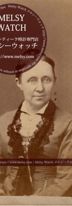 ネックレスから腰のポケットに懐中時計を収めている女性の写真 【1900年頃】-I4080
