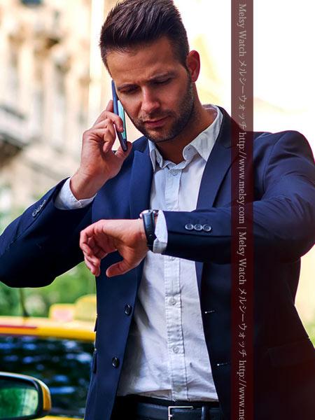 電話をしながら時計を見る男性