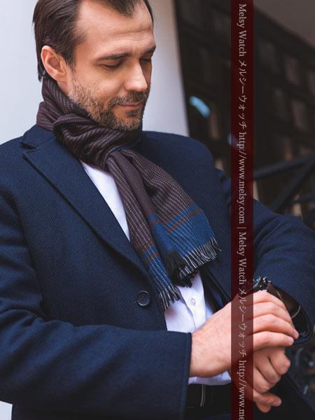 マフラーとコートを羽織る紳士と腕時計