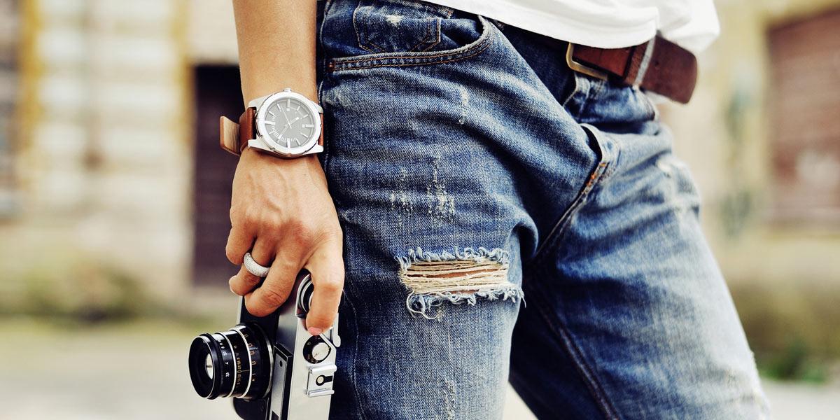 ジーンズ姿に腕時計とカメラ