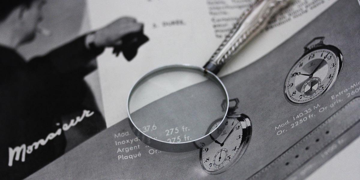 古い時計広告と虫眼鏡