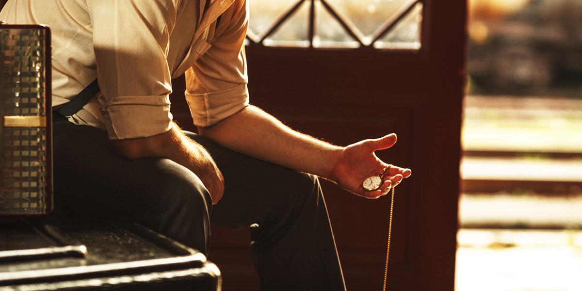 手のひらに懐中時計を載せる男性