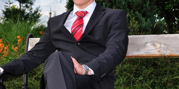 椅子に掛けるスーツ姿の男性