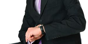 腕時計を見るスーツ姿の男性
